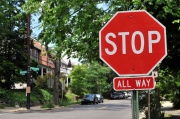 A stop sign (foreground) with cars across the street